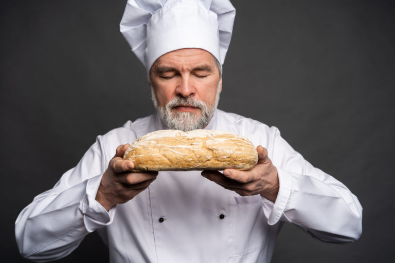 Portrait,Of,A,Male,Chef,Cook,Smelling,Fresh,Bread,Against