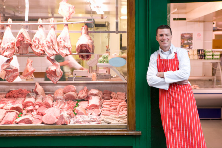 A,Young,Smiling,Butcher,In,Red,Apron,Leaning,Against,Butcher